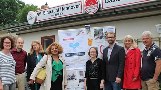 Eine Gruppe von acht Personen steht für den Vereinsheim des VfL Eintracht Hannover