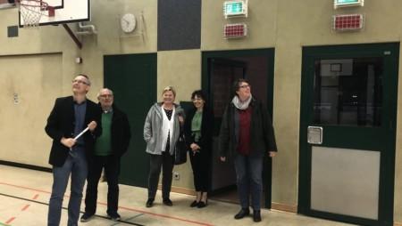 Drei Frauen und zwei Männer stehen in einer Sporthalle und schauen umher