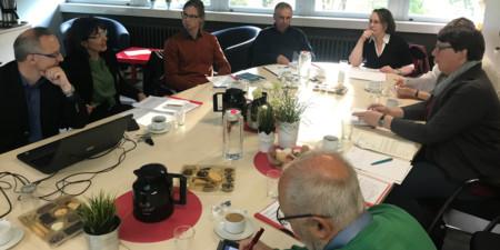 Mehrere Personen sitzen um einen Konferenztisch und diskutieren.