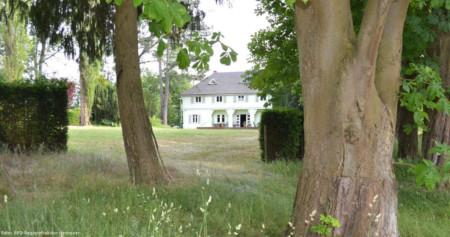 Blick zwischen Baumstämmen hindurch, über eine Wiese auf das Gebäude des Hermannshofs