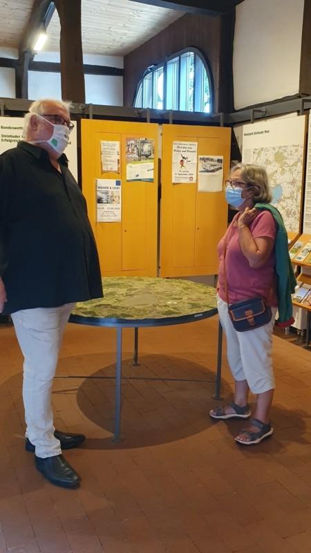 Eine Frau und ein Mann stehen in einem Ausstellungsraum des Infozentrums