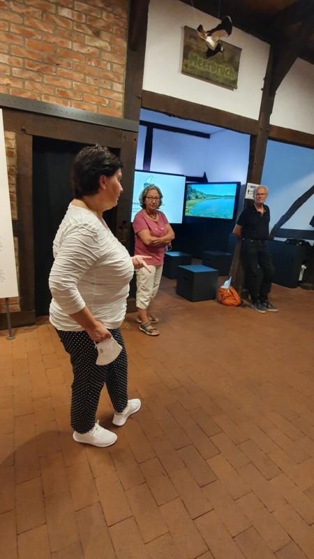 Zwei Frauen und ein Mann stehen in einem Ausstellungsraum im Infozentrum