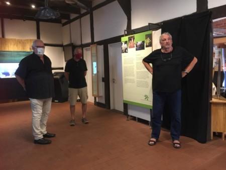 Drei Männer stehen  in den Ausstellungsräumen des Infozentrums
