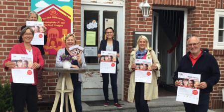 Fünf Frauen und ein Mann halten vor dem Eingang des DorfTreffs Plakate der AWO Frauenberatungsstelle hoch