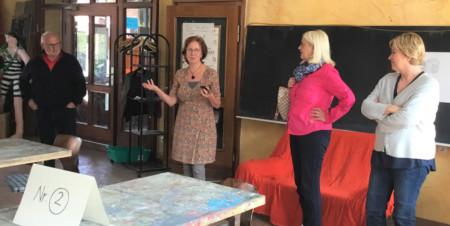 Eine Frau zeigt und erklärt zwei weiteren Frauen und einem Mann einen Werkstattraum