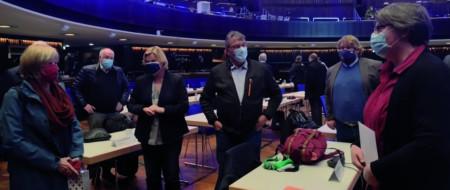 Menschen mit Mund-Nasen-Schutz stehen mit Abstand im Kuppelsaal des HCC