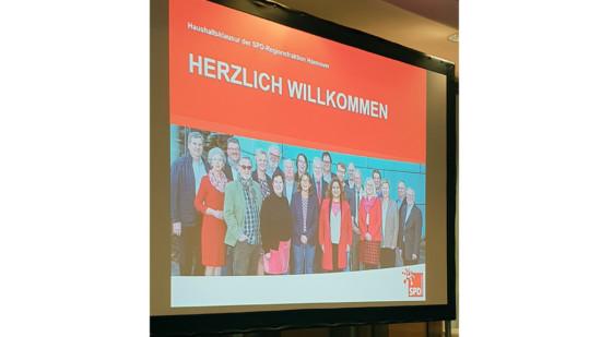 Foto einer Leinwand, darauf das Gruppenbild der Regionsfraktion und geschrieben: Haushaltsklausur der SPD-Regionsfraktion Hannover - Herzlich willkommen