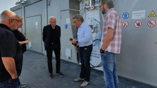 Vier Personen lassen sich vor einer technischen Anlage im Außenbereich ein technisches Gerät erläutern