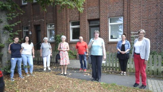 Acht Personen stehen vor einem Haus