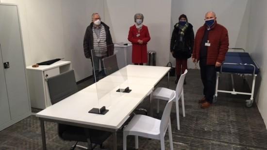 Vier Personen mit Mund-Nasen-Schutz stehen nebeneinander hinter einem Tisch mit zwei Stühlen in einem Behandlungsraum