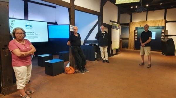 Eine Frau und drei Männer stehen in einem Ausstellungsraum des Infozentrums