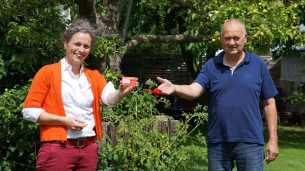 Eine Frau und ein Mann stehen nebeneinander in einem Garten und zeigen eine rote Karte im Scheckkartenformat