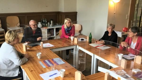 Fünf Personen sitzen mit Abstand und Spuckschutzwänden an Tischen und unterhalten sich