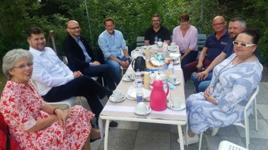 Neun Personen sitzen draußen um einen Tisch