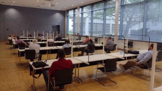 Mehrere Personen sitzen in einem Sitzungsraum