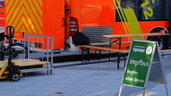Ein grünes Schild mit der Aufschrift: Impfbus - Impfen ohne Termin steht vor einem Feuerwehrwagen